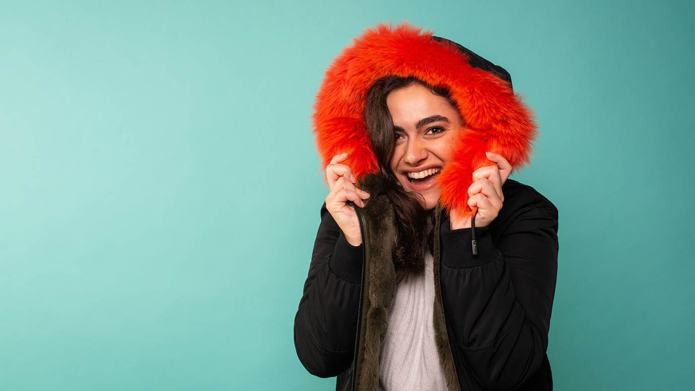Sevinc smiles at the camera against a pale turquoise backdrop. She has a bright red faux fur lined hood up.