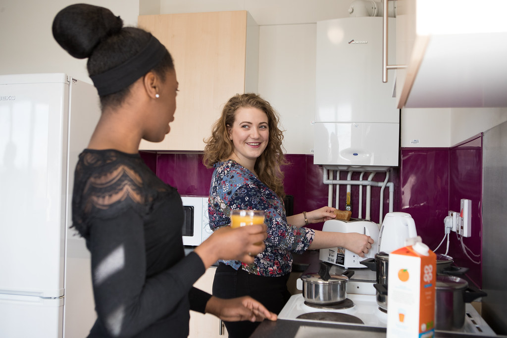 Students in their accommodation kitchen playing a game
