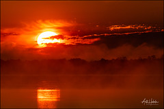Hot Sun is rising through the clouds and morning mist