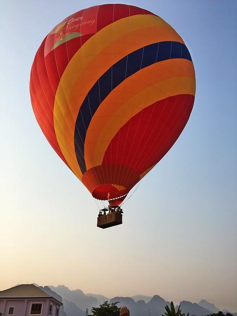 A hot air balloon lifting off into the sky of Vang Vieng, Laos