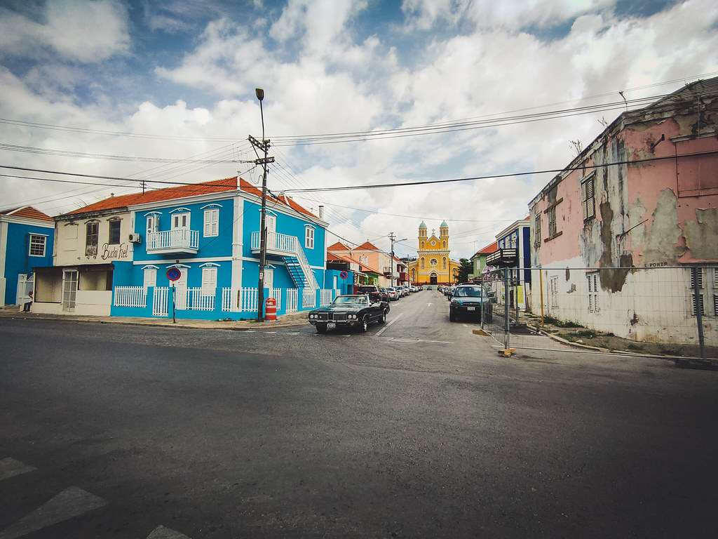 Street photo of old buildings, blue, worn down. A yellow church at the end of the street and cars on the street