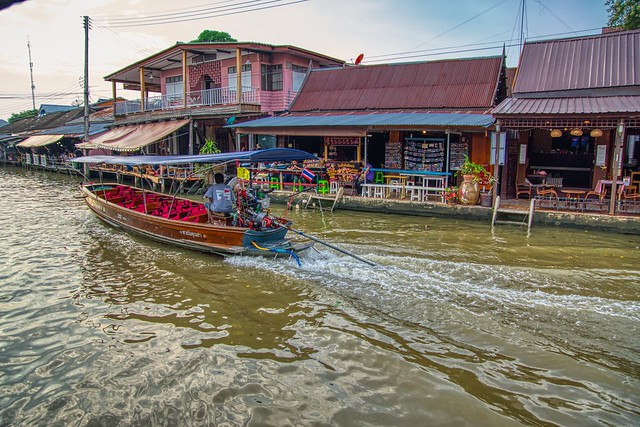 Amphawa floating market with passing boat in Samut Songkhram province in Thailand