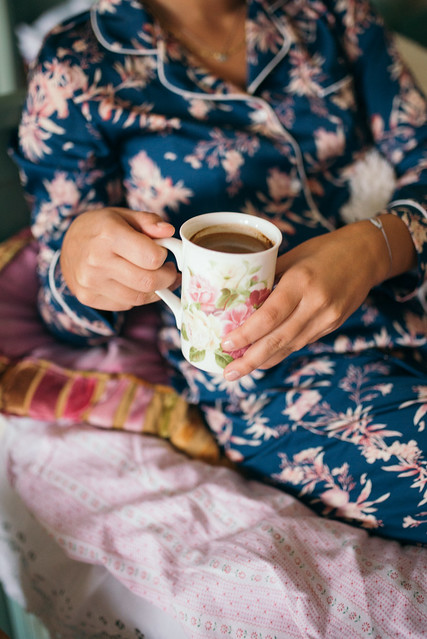 Young woman in pajamas drinking coffee in bed.
