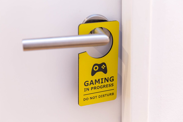 A gamer's room: white door with yellow