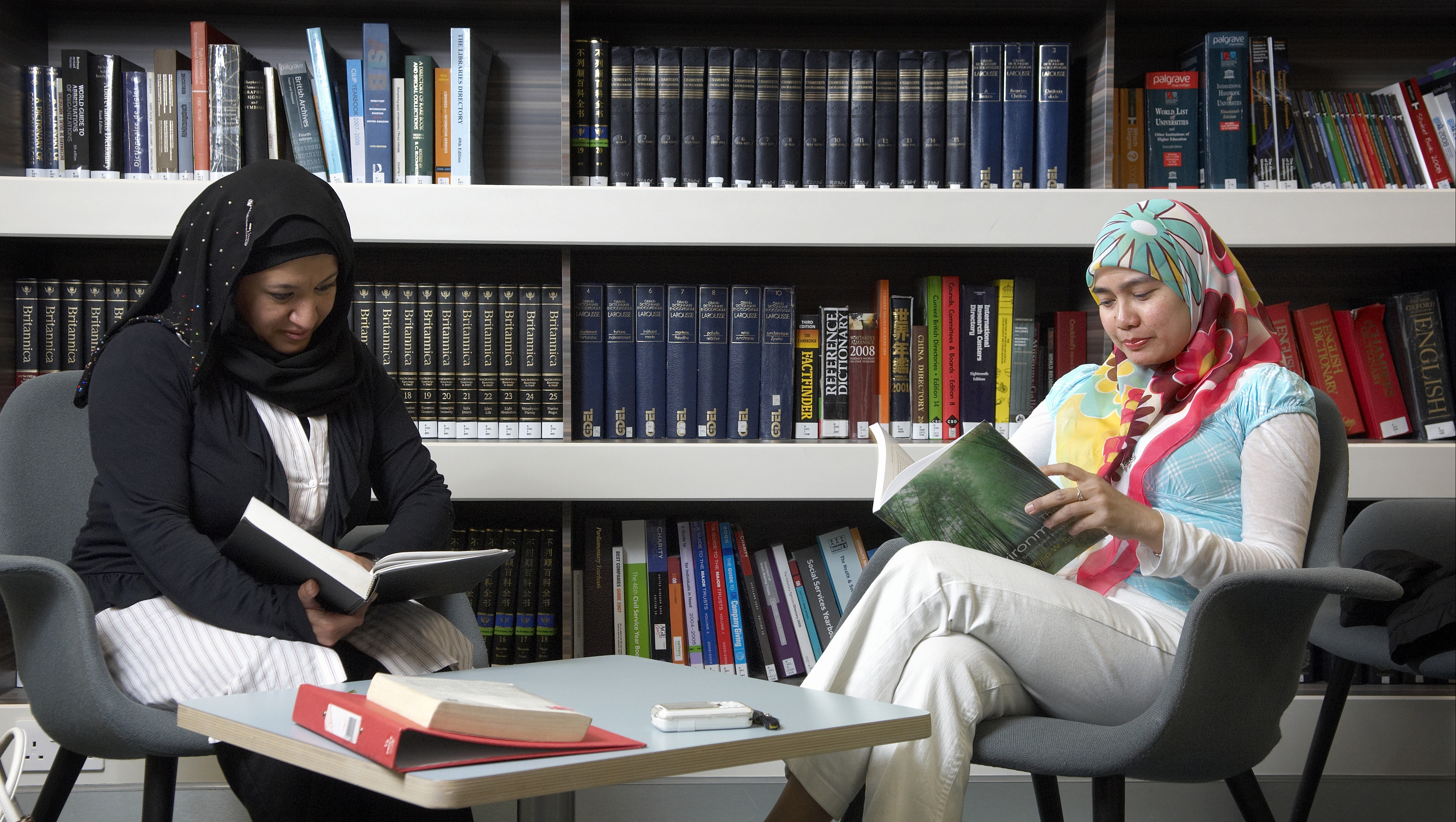 Two students read in the library