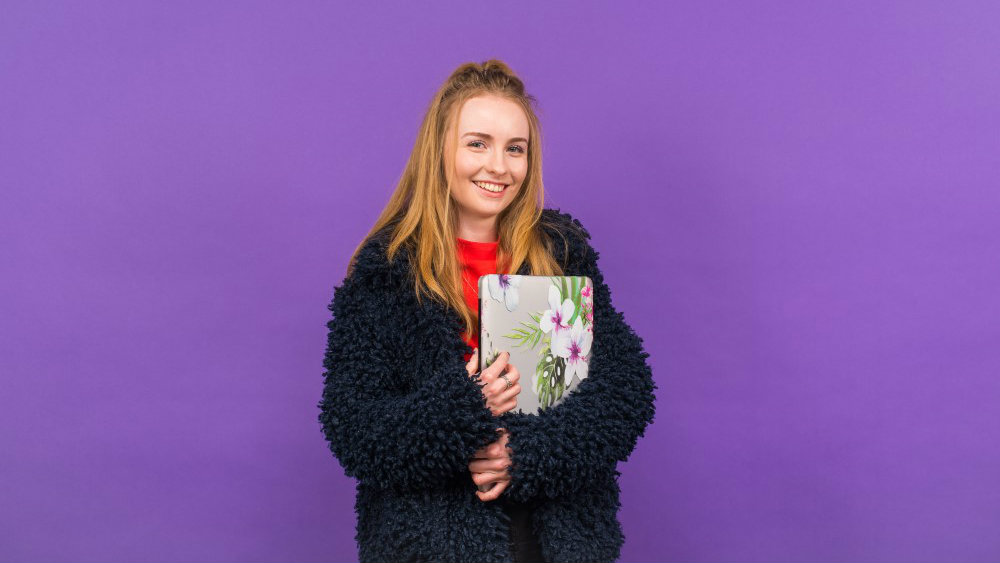 Photo of Ellie against a purple background. She has long blond hair, wearing a fluffy black coat over a red top and is holding a laptop in a flowered cover.