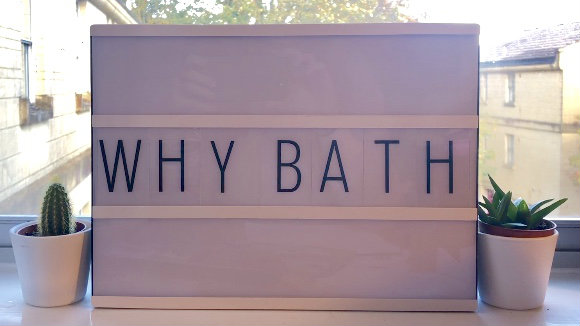 The words Why Bath in black capitals on a light-coloured block of wood. There  are two house plants either side of the block and you just about make out some trees and the sky in the backgound.d