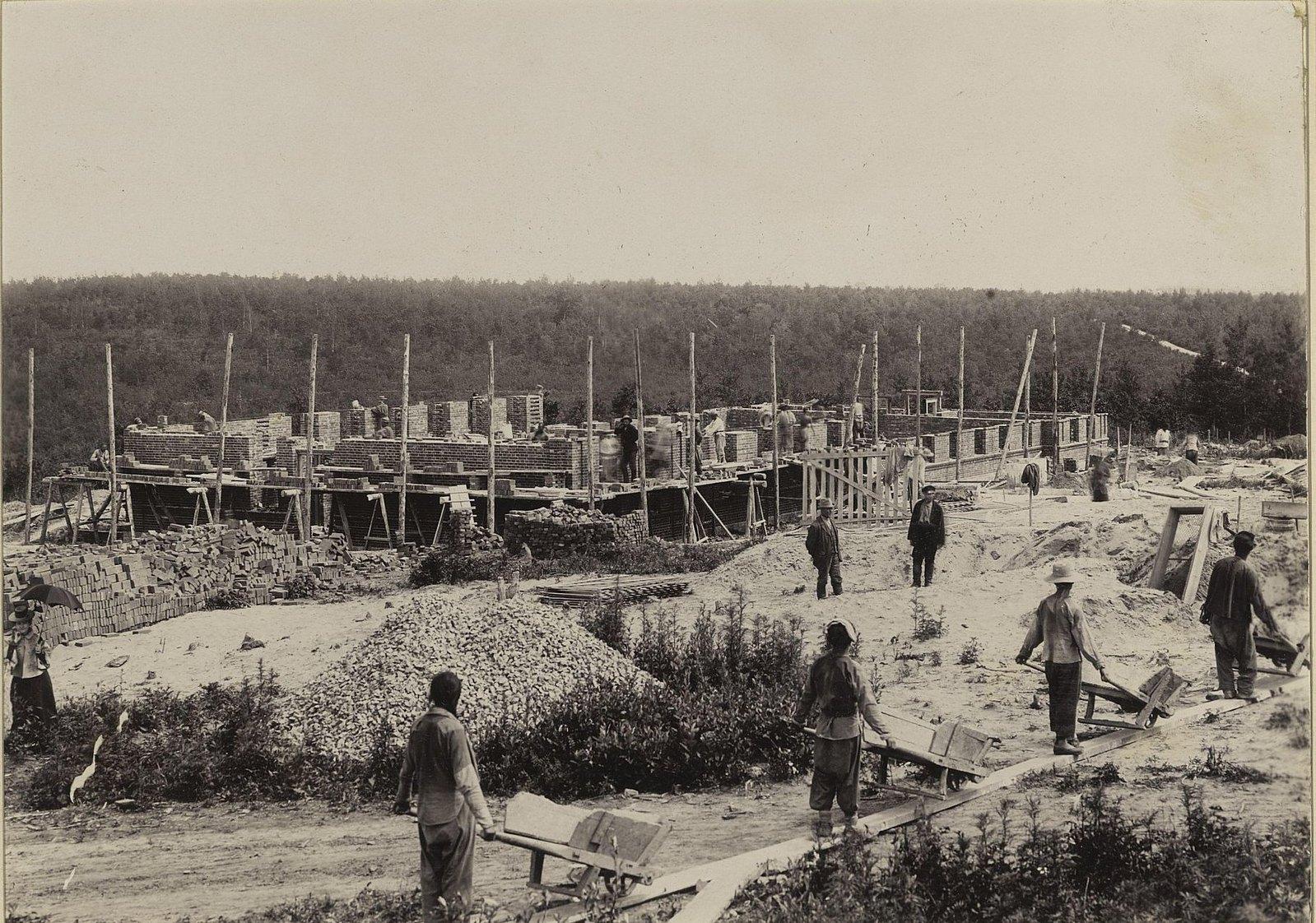 Рабочие везут тачки на участке строительства