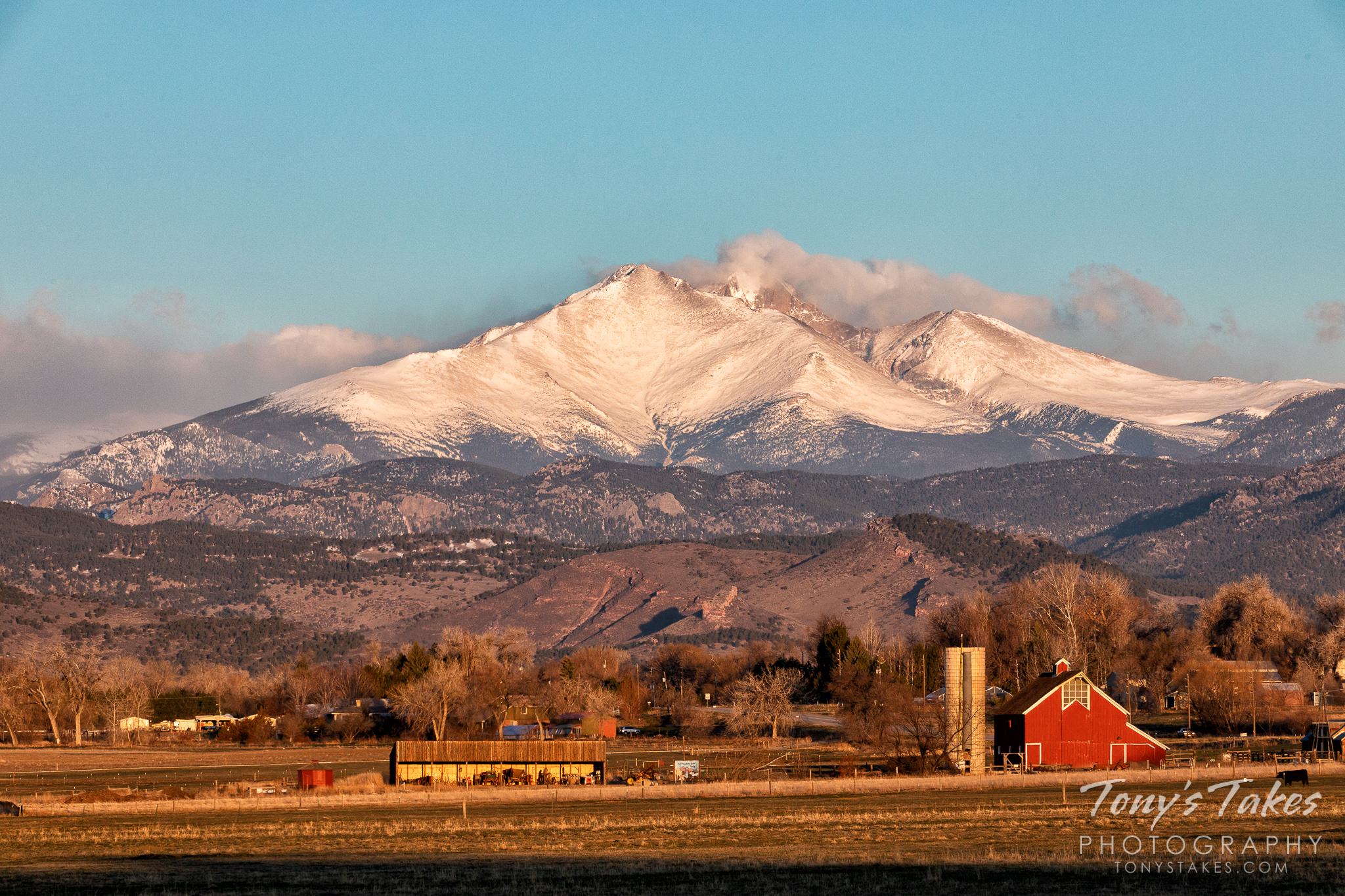 A bright, red barn stands on the lower elevations while behind, Mount Meeker and Longs Peak tower above. (© Tony's Takes)