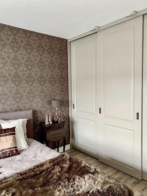 Behang met patroon sprei bed kast met schuifdeuren slaapkamer