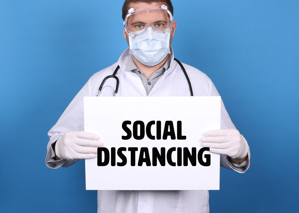 Social Distancing. Doctor holding message sign for COVID-19 Pandemic at blue background