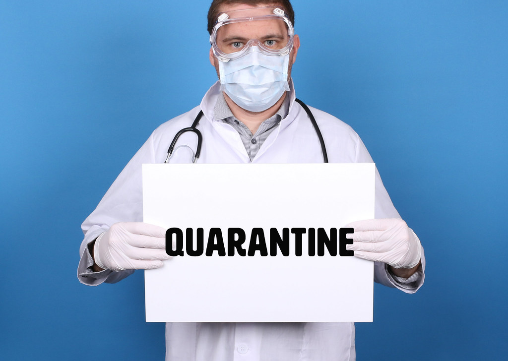 Coronavirus Quarantine. Doctor holding message sign for COVID-19 Pandemic at blue background