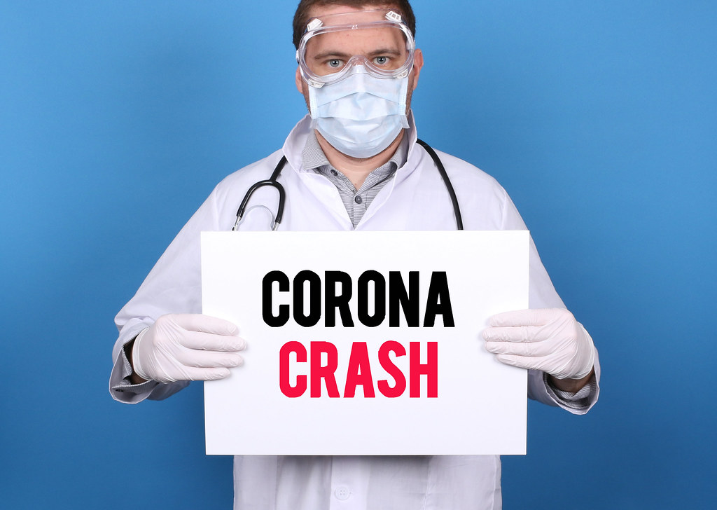 Corona Crash. Doctor holding message sign for COVID-19 Pandemic at blue background
