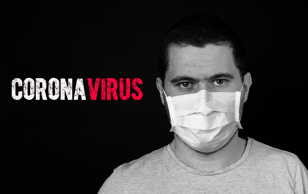 Man in medical face protection mask indoors on black background with Coronavirus text