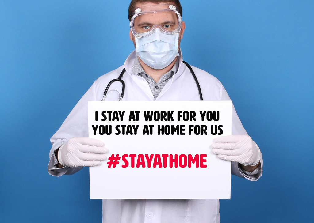 Stayathome. Doctor holding message sign for COVID-19 Pandemic at blue background