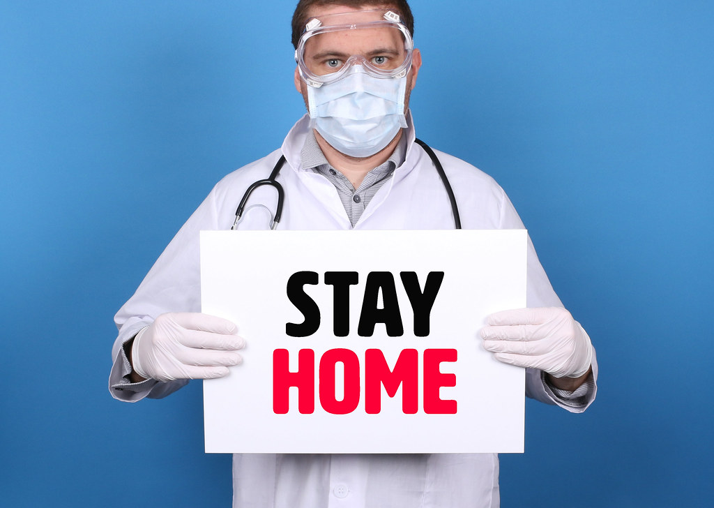 Stay Home. Doctor holding message sign for COVID-19 Pandemic at blue background