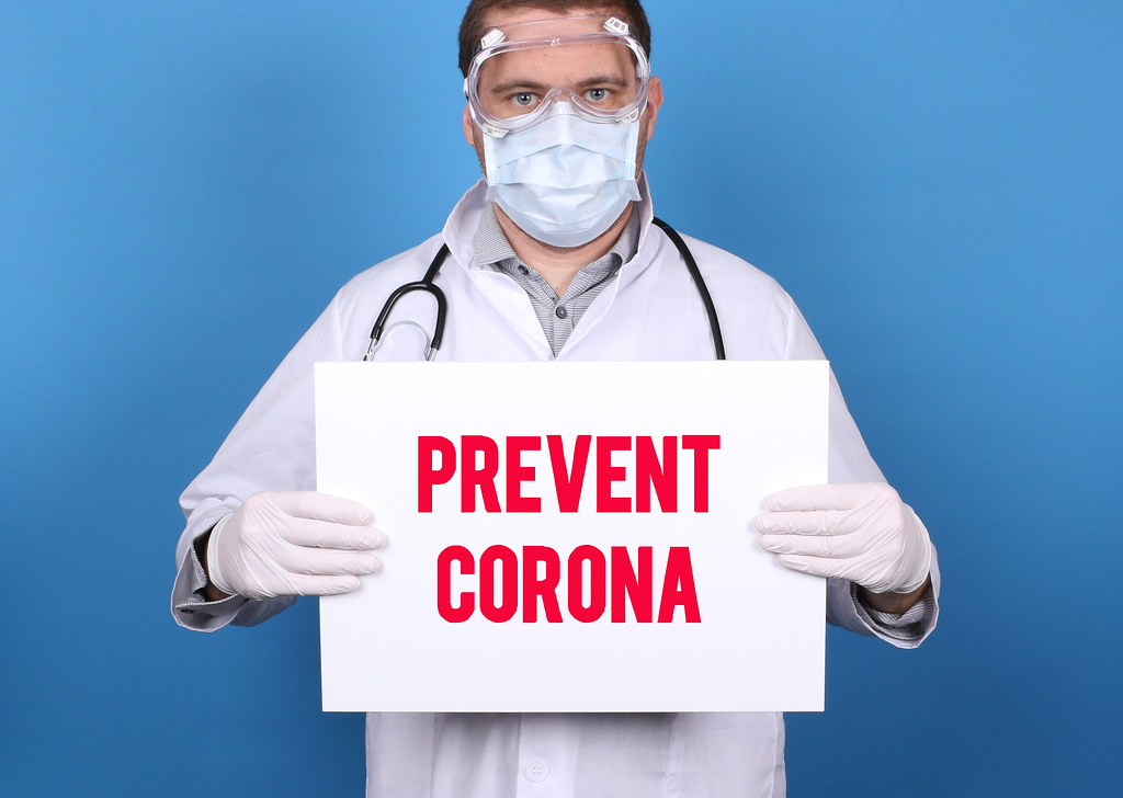 Prevent Corona. Doctor holding message sign for COVID-19 Pandemic at blue background