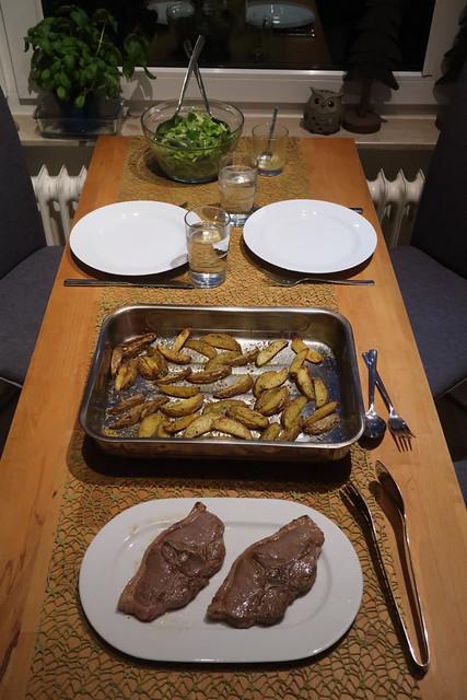 Lammkoteletts mit Rosmarinkartoffelecken und Blattsalat (Tischbild)