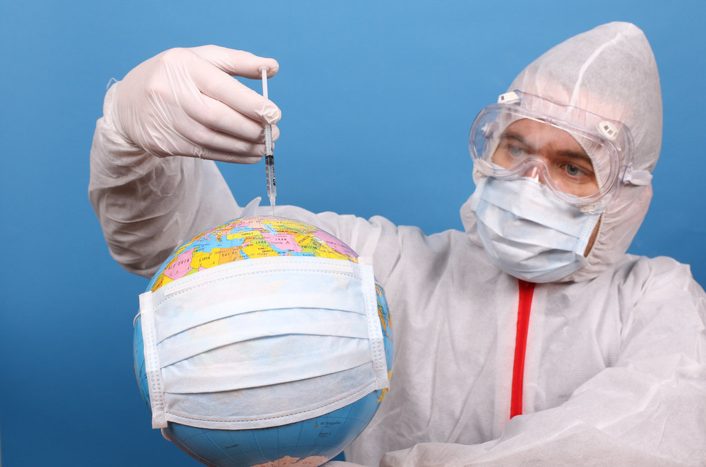 Stop coronavirus concept. Earth planet in protective medical mask and a disposable syringe