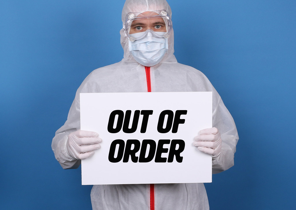 Medical worker in protective suit holding a sign with Out Of Order text