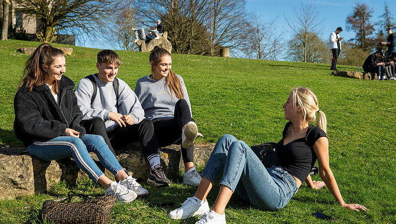 A group of students sitting on the grass on campus