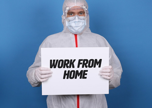 Medical worker in protective suit holding a sign with Work From Home text | by focusonmore.com