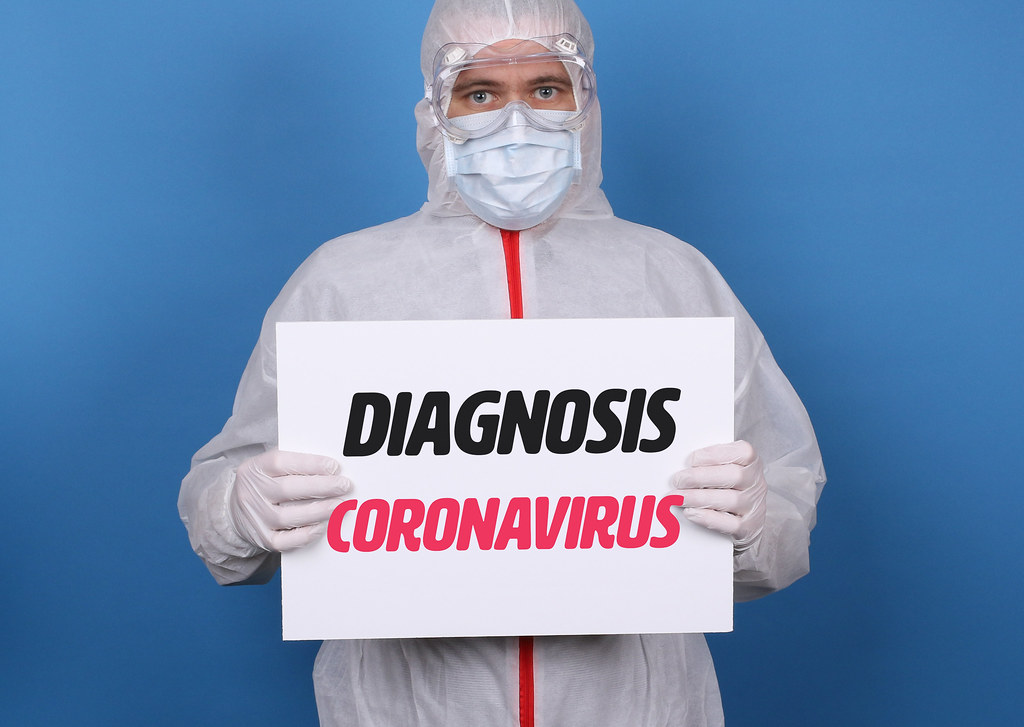 Medical worker in protective suit holding a sign with Diagnosis Coronavirus text