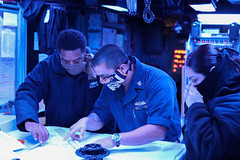 Sailors aboard USS Makin Island (LHD 8) review charts in the combat information center during operations in the Pacific, April 7. (U.S. Navy/MC3 Jacob D. Bergh)