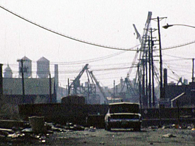 More 1970s fun from the good old days!  A low-res frame from a Super 8 movie showing a stripped car surrounded by trash near the bank of the Morris Canal. Ellis Island water towers at left. A crane graveyard rounds out the scene. Jersey City. April 1976