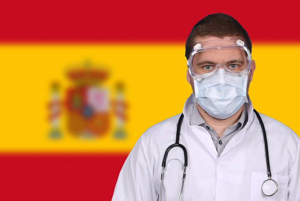 Doctor in protective medical mask over flag of Spain