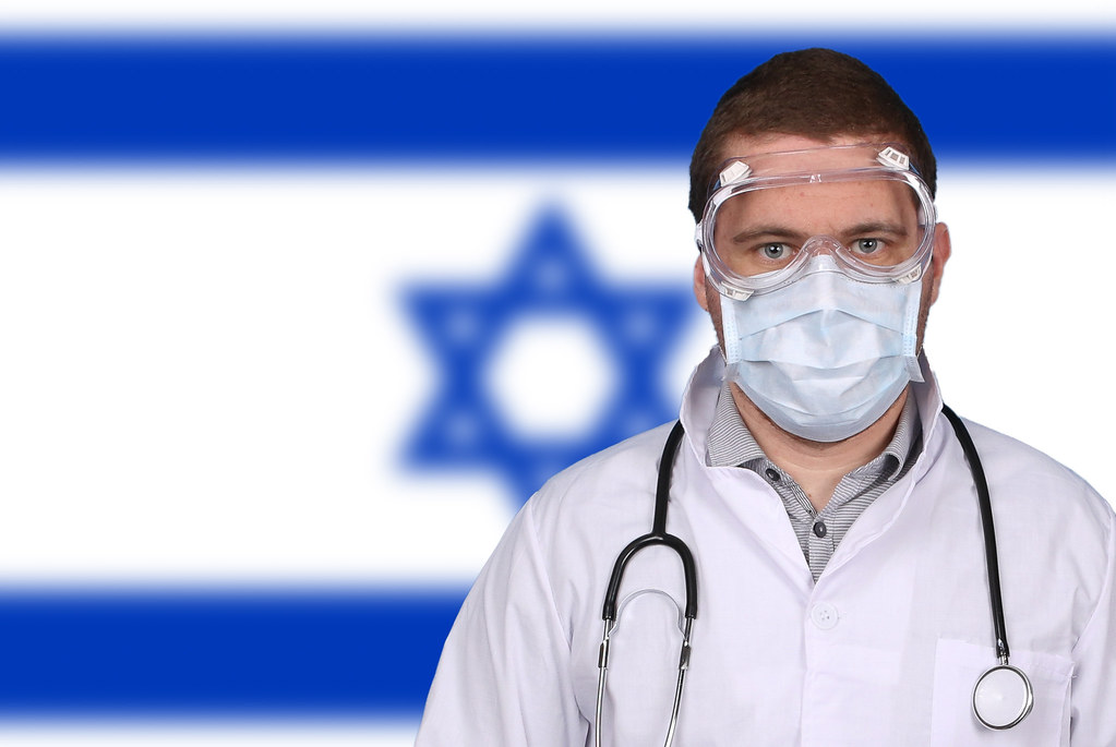 Doctor in protective medical mask over flag of Israel
