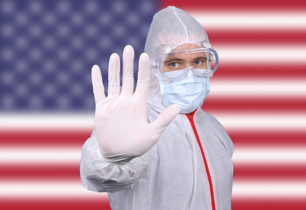 Doctor or Nurse Wearing Medical Personal Protective Equipment (PPE) Against The Flag Of USA