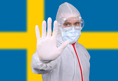 Doctor or Nurse Wearing Medical Personal Protective Equipment (PPE) Against The Flag Of Sweden