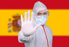 Doctor or Nurse Wearing Medical Personal Protective Equipment (PPE) Against The Flag Of Spain