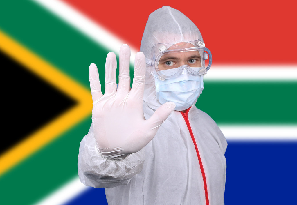 Doctor or Nurse Wearing Medical Personal Protective Equipment (PPE) Against The Flag Of South Africa