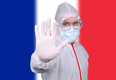 Doctor or Nurse Wearing Medical Personal Protective Equipment (PPE) Against The Flag Of France