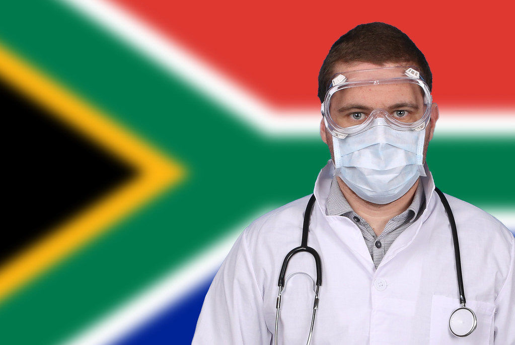 Doctor in protective medical mask over flag of South Africa