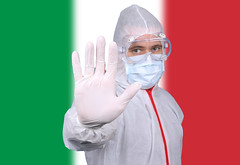 Doctor or Nurse Wearing Medical Personal Protective Equipment (PPE) Against The Flag Of Italy