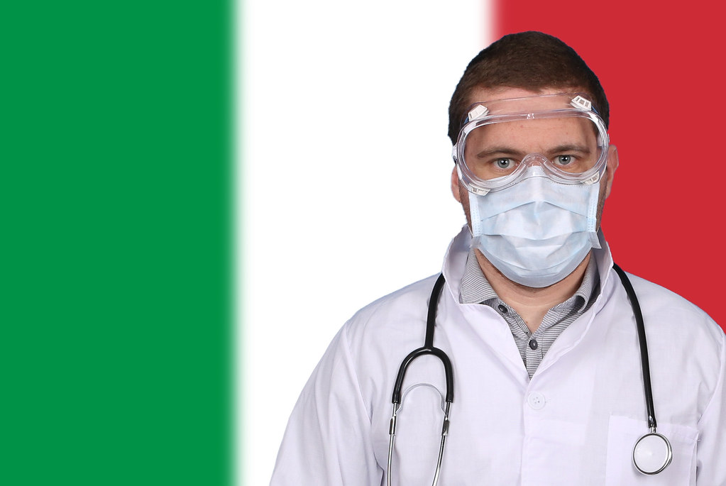 Doctor in protective medical mask over flag of Italy