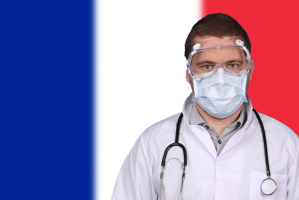 Doctor in protective medical mask over flag of France