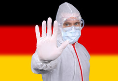 Doctor or Nurse Wearing Medical Personal Protective Equipment (PPE) Against The Flag Of Germany