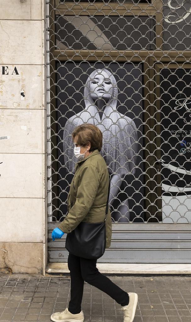 Covid-19.Mujer y cartel.Avda.del Cid.València