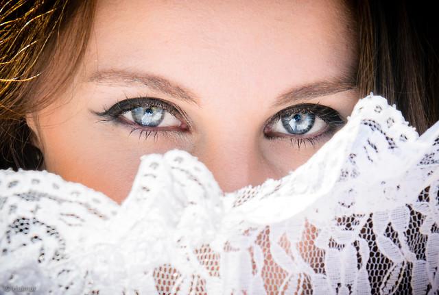 Bride peering over her lace umbrella