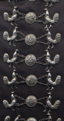 A close-up shot of the silver 'rooster' Mariachi buttons on black costume pants