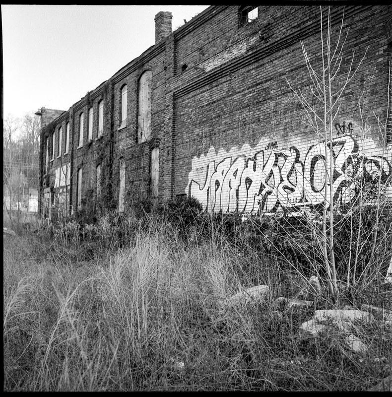 exterior, abandoned mill, graffiti, urban landscape, River District, Asheville, NC, Ricohflex Dia M, Bergger Pancro 400, HC-110 developer, late March 2020