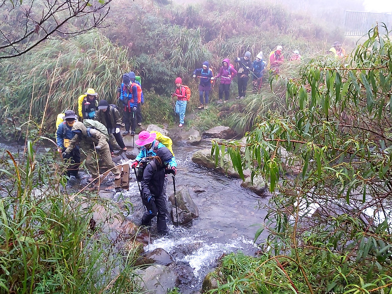 Guides helping hikers cross the river