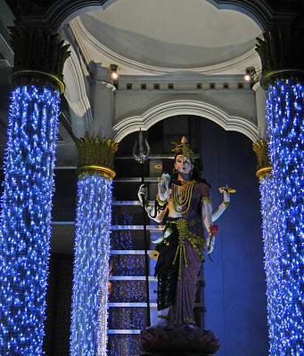 Blue lights brighten up the pillars of a small temple containing a goddess in Bangkok, Thailand