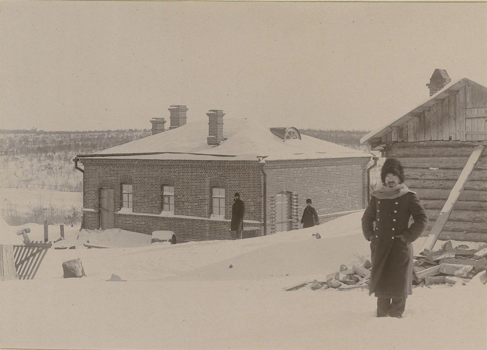 Три человека у зданий Хабаровской окружной артиллерийской мастерской