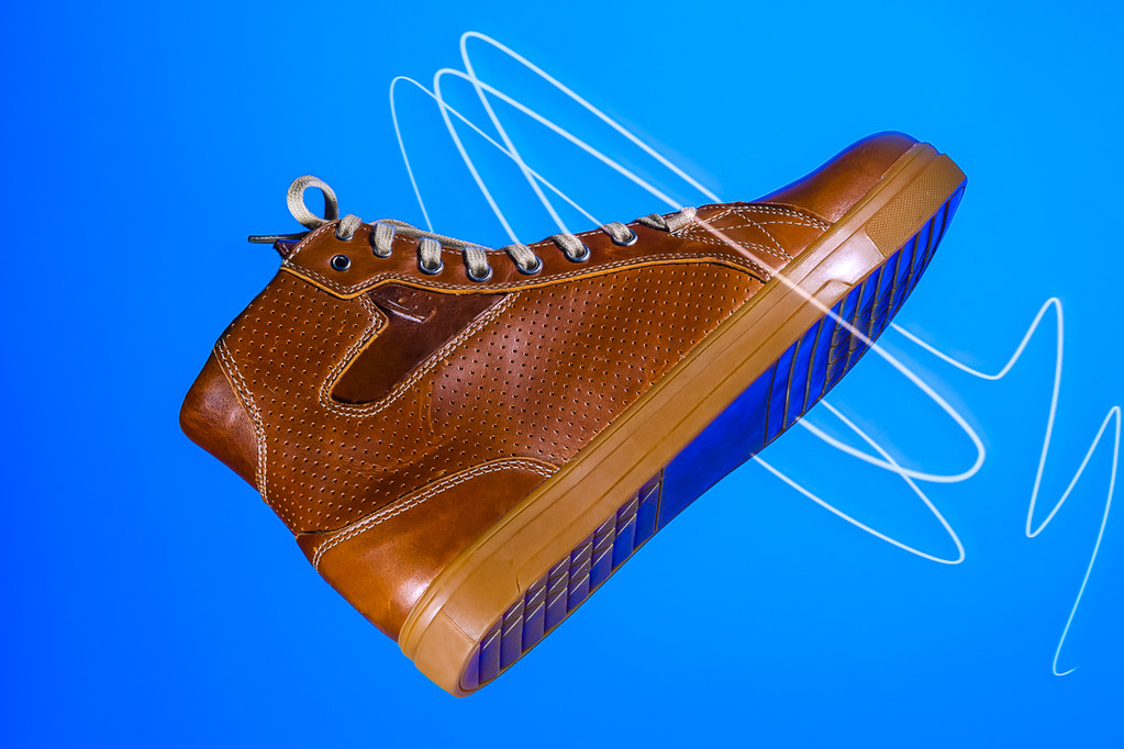 Closeup of Motorcyclist Tan Leather Protective Boots. Against Blue Background.