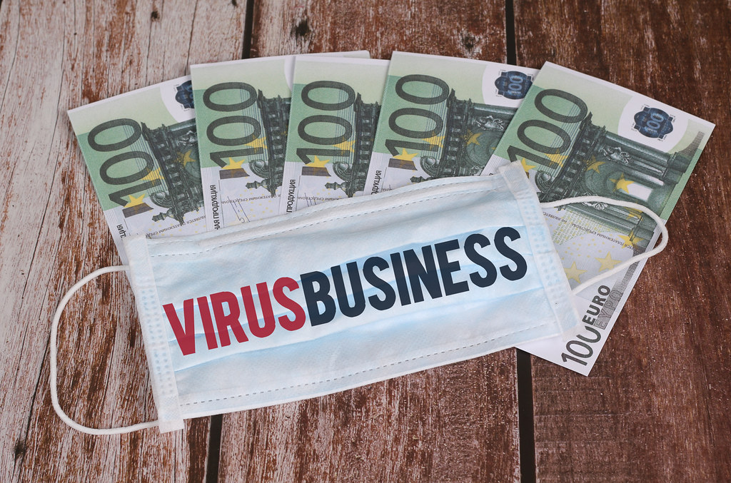 Medical face mask and money with Virus Business text. World coronavirus epidemic and economic damages.